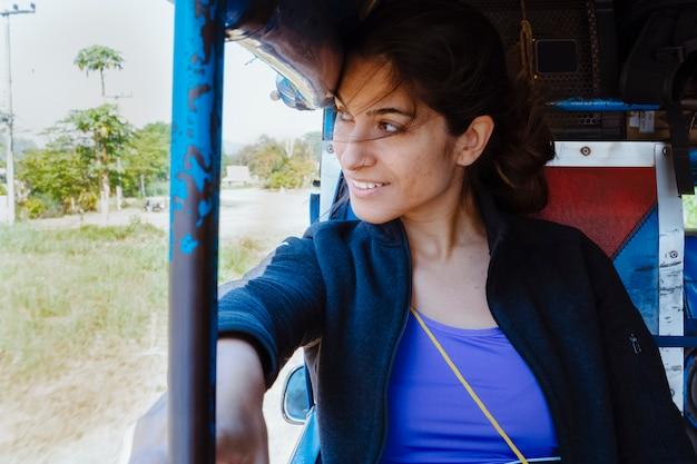 タイの公共交通機関で旅行する女性バックパッカー。ソンテウはアジア諸国間を移動する安価な方法です。観光客はアジアの真の南東を体験します。休日や旅行のコンセプトです。
