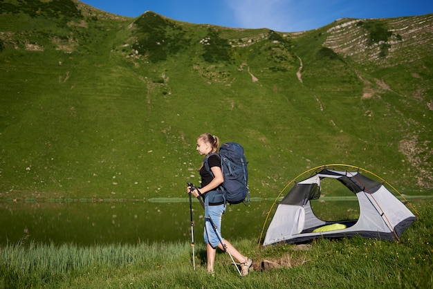 Woman backpacker with backpack and trekking sticks near tent, enjoying summer day near the lake in the mountains