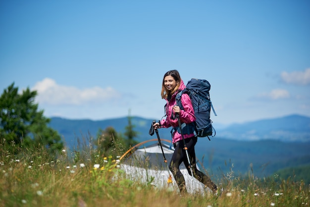 Woman backpacker with backpack and trekking sticks near tent, walking on the top of a hill against blue sky, enjoying sunny day in the mountains.