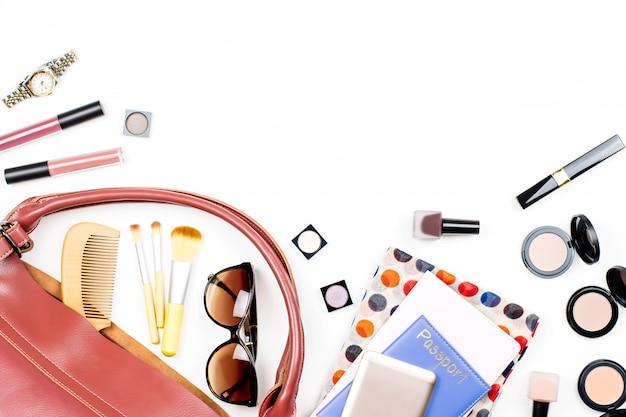 女性バッグのもの、旅行の概念。美容製品、流行のアクセサリー、パスポート、スマートフォン、コピースペース