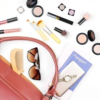 女性バッグのもの、旅行の概念。美容製品、流行のアクセサリー、パスポート、スマートフォン