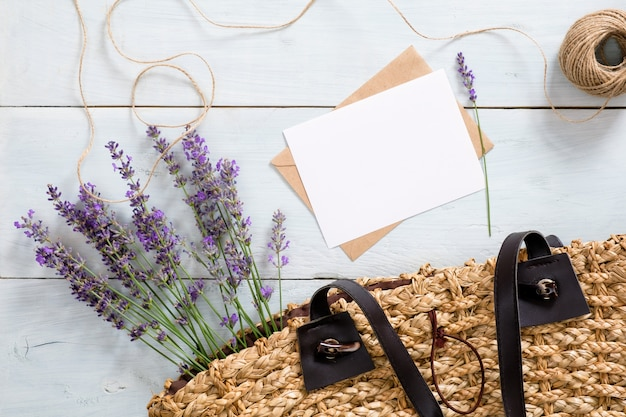 Woman bag with lavender flowers, blank paper card and envelope on blue wooden desk