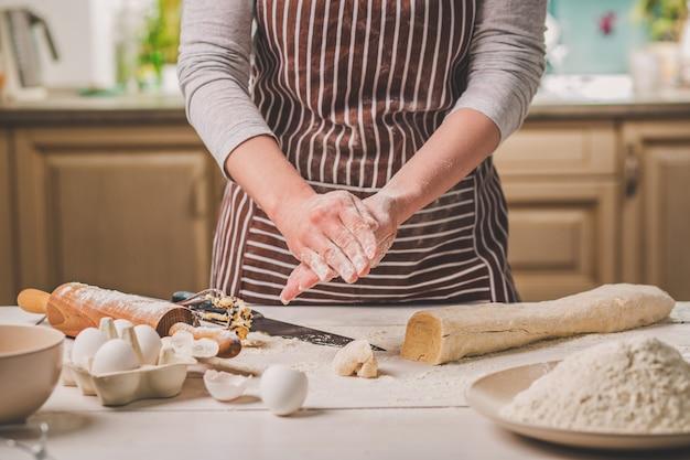 여자는 파이를 굽는다. 과자 장수는 디저트를 만듭니다. 빵 만들기. 테이블에 반죽입니다. 반죽을 반죽하십시오. 줄무늬 앞치마를 입은 여성이 부엌에서 요리를 하고 있다
