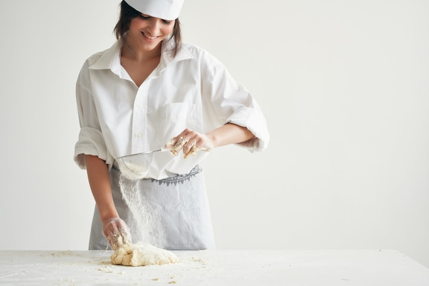 Woman baker in chef uniform cooking food kitchen flour products