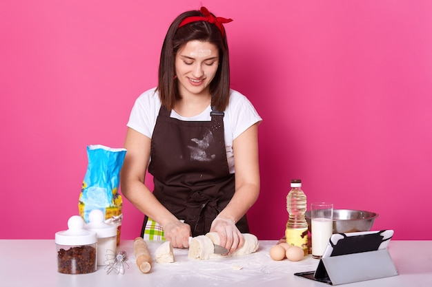 Woman baker cuts dough in small parts, ready for sculpting hot cross buns, make pies from dough, wears brown apron, casual white t shirt, red hair band, posing isolated over pink wall.