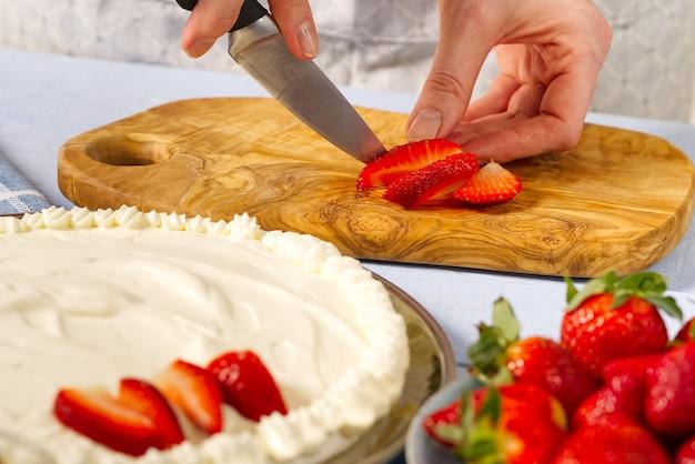 여자 베이커 손은 머랭과 크림으로 만든 집에서 만든 케이크를 위해 딸기를 잘라
