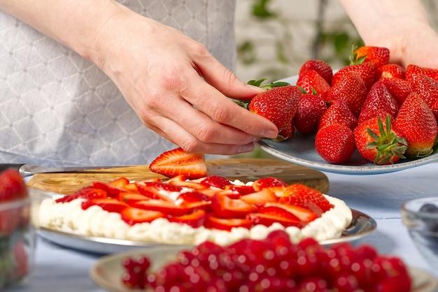여자 베이커 손은 머랭과 크림으로 만든 집에서 만든 딸기 케이크를 위해 딸기를 잡아