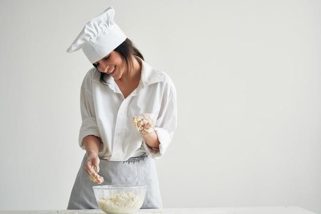 クックユニフォームの女性パン屋は生地粉製品で動作します