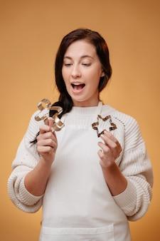 Женщина-пекарь в удивлении держит формочки для рождественского печенья на желтом фоне, пряники