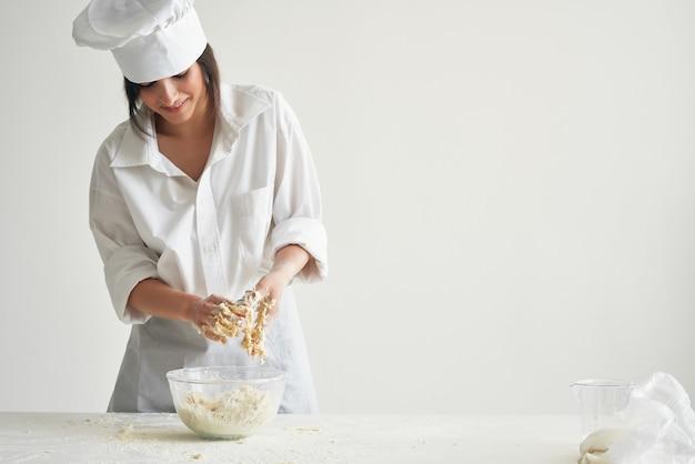 テーブルの上の生地をこねる女性パン屋プロの仕事
