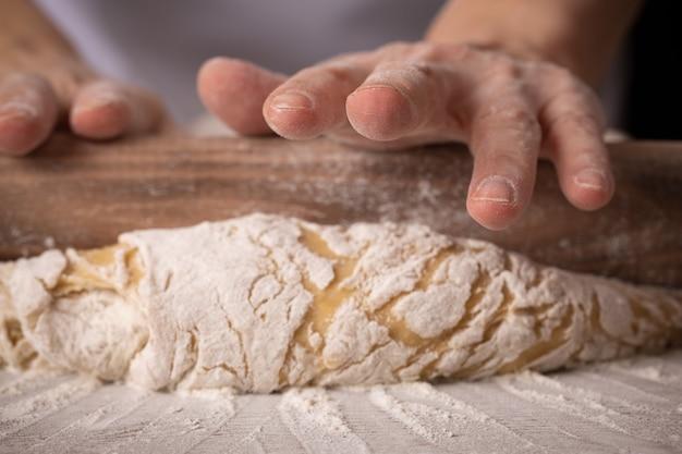 여자 베이커는 빵집에서 반죽을 롤아웃합니다.