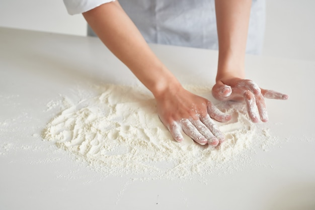 女性のパン屋は小麦粉で働く生地を広げます