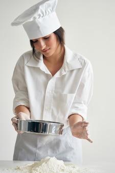 女性パン屋は小麦粉調理ミールペストリーをふるいにかける