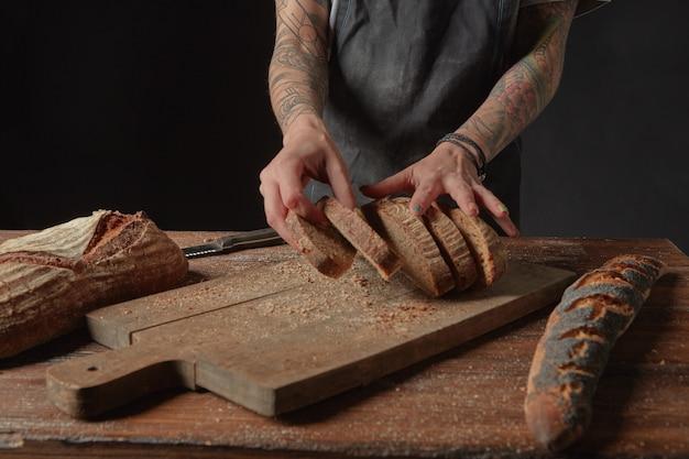 Женщина-пекарь с татуировками на руках, нарезанный хлеб из отрубей на деревянном столе