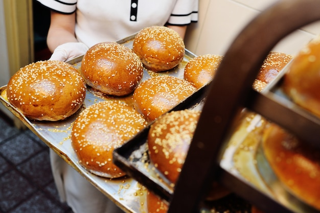 ゴマとハンバーガーの新鮮な丸いパンのトレイを保持している女性ベーカリー労働者をクローズアップ