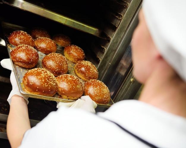 ゴマ種子のクローズアップとハンバーガーの新鮮な丸パンのトレイを保持している女性ベーカリー労働者