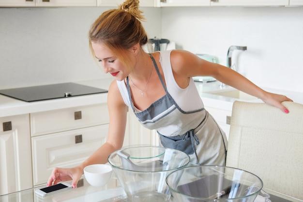 Женщина печет торт на кухне и видит рецепт для смартфона