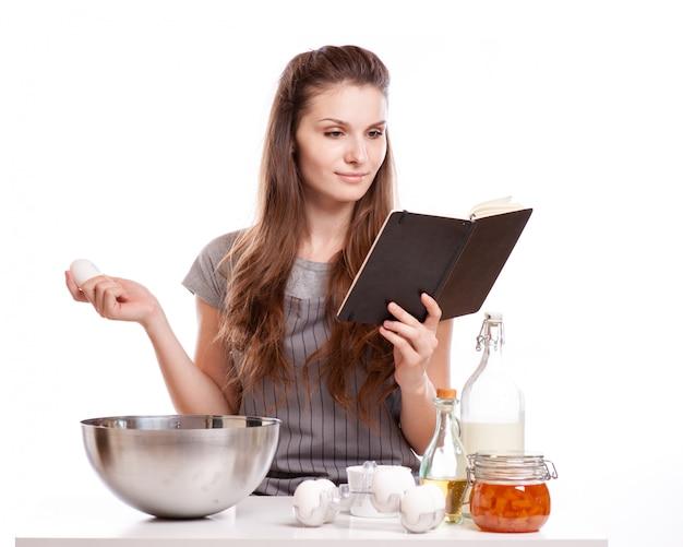 Woman baking at home following recipe