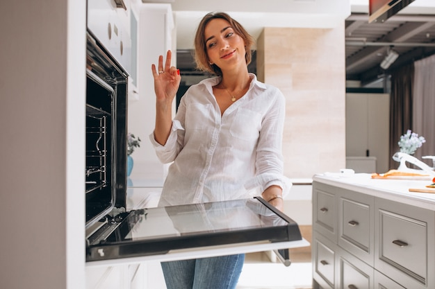 Woman baking at kitchen and looking into the oven