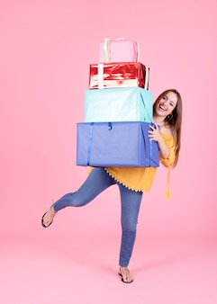 Woman balancing stack of gift boxes on pink background