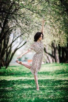 Woman ballerina in blooming garden. pink. ballet. portrait of dancing girl outdoor. fashion and style