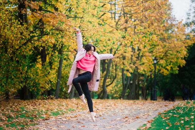 여자 발레리나 황금 가을 공원에서 pointe 신발 춤, 발레에 서 노란색 잎에 포즈