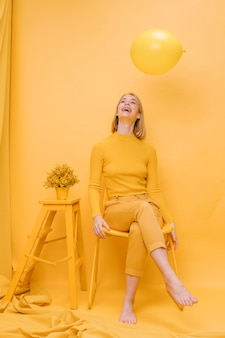 Woman and balloon in a yellow scene
