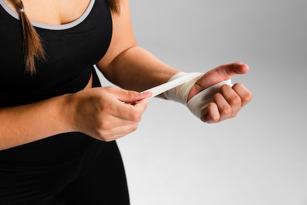 Woman bandaging her hands sideways