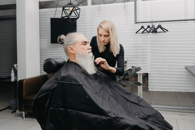 Woman barber cutting hair to an aged bearded man
