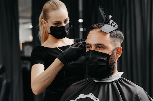 Женщина парикмахерская стричь волосы для бородатого мужчины в маске. карантинная прическа концепции.