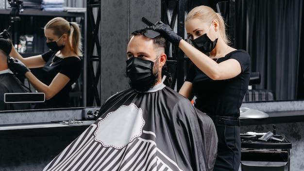 女性は理髪店でひげを生やした男性に髪をカットします。隔離散髪コンセプト。
