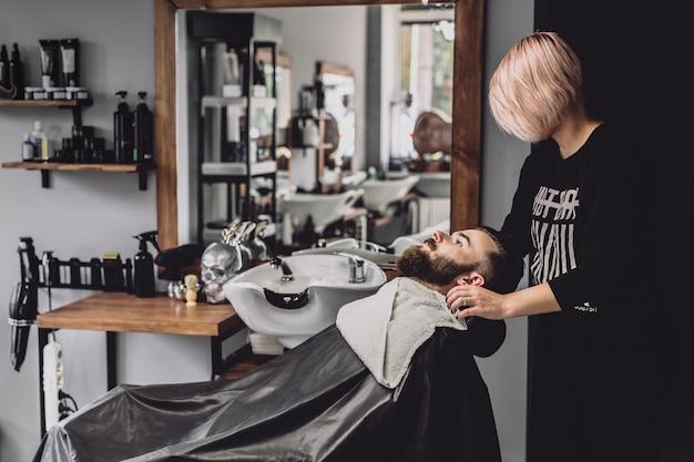 女性理髪店は治療のためのクライアントを準備する