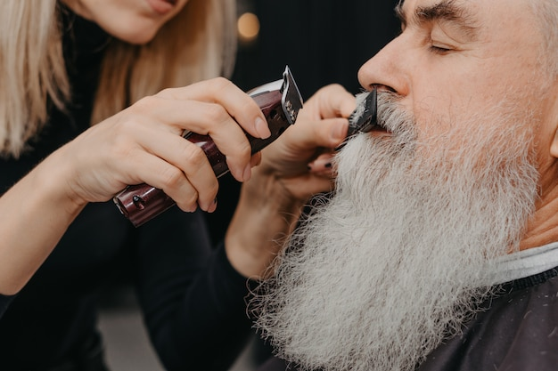 Woman barber trimming mustache to an aged bearded man
