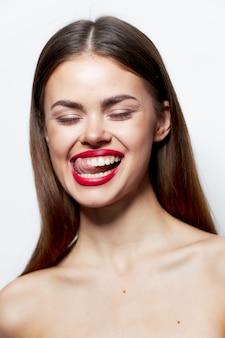 Женщина с открытыми плечами и закрытыми глазами показывает язык естественный свет