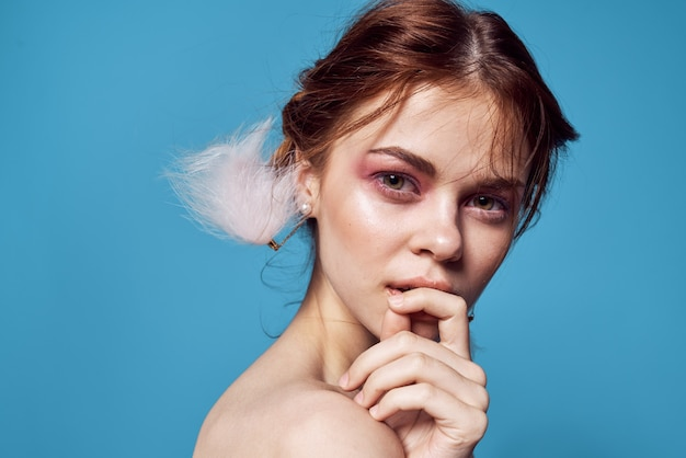 여자 벌거 벗은 어깨 솜털 귀걸이 화장품 럭셔리 파란색 배경