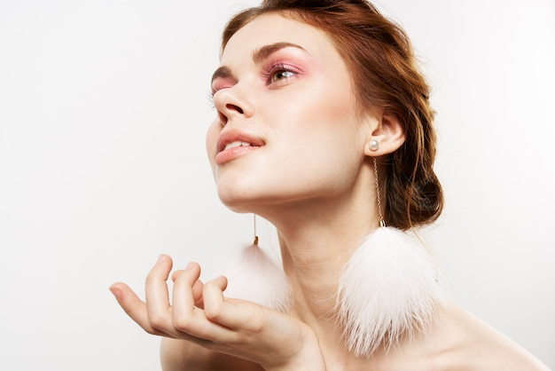 Woman bare shoulders fluffy earrings pure skin cosmetics