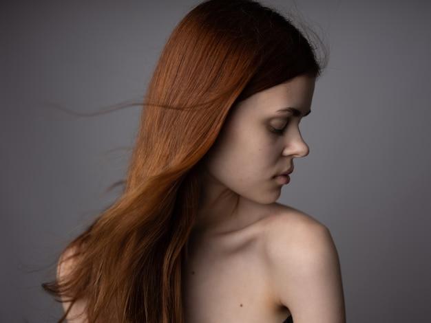女性の裸の肩の灰色の壁の緩い髪のモデル