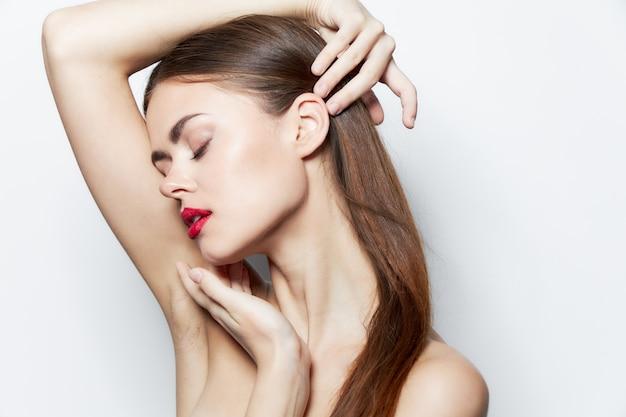 Женщина с голыми плечами, держащая руку на голове, с закрытыми глазами, красные губы, яркий макияж