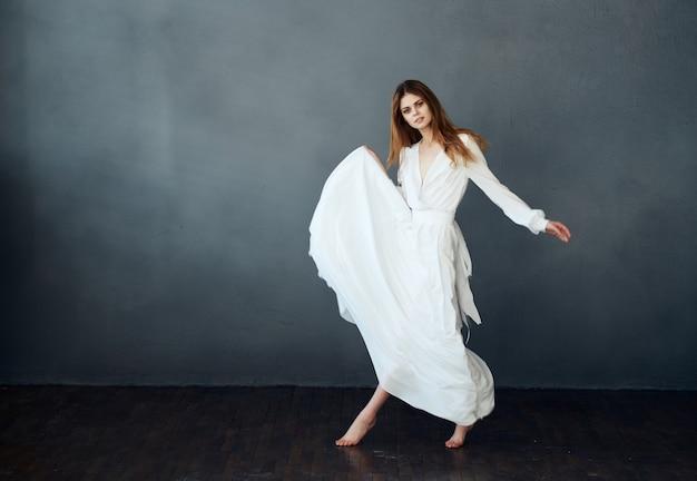 어두운 배경에서 춤을 추는 하얀 드레스를 입은 맨발의 여자
