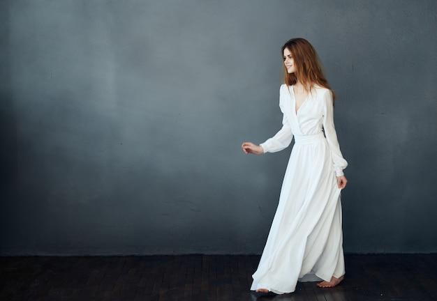 孤立した背景のロマンスで踊る白いドレスを着た裸足の女性