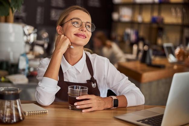 Woman barista felling happy in coffee shop