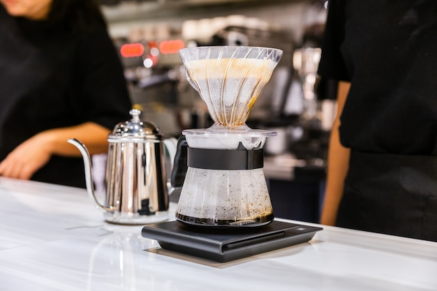 Женщина-бариста делает разливной кофе альтернативным методом под названием «капание». кофемолка, подставка для кофе и налив на мраморной столешнице.