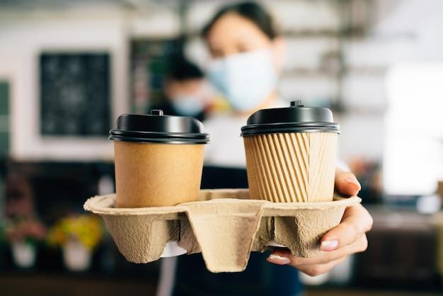 コーヒーショップで持ち帰り用の紙の使い捨てカップでコーヒーを提供するフェイスマスクを身に着けている女性バリスタ