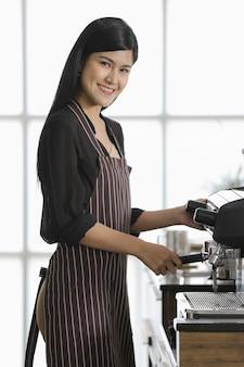 コーヒーメーカーの前に立ってエプロンを着て、自信を持ってフレンドリーな方法でコーヒーショップで飲み物を作る女性バリスタ。