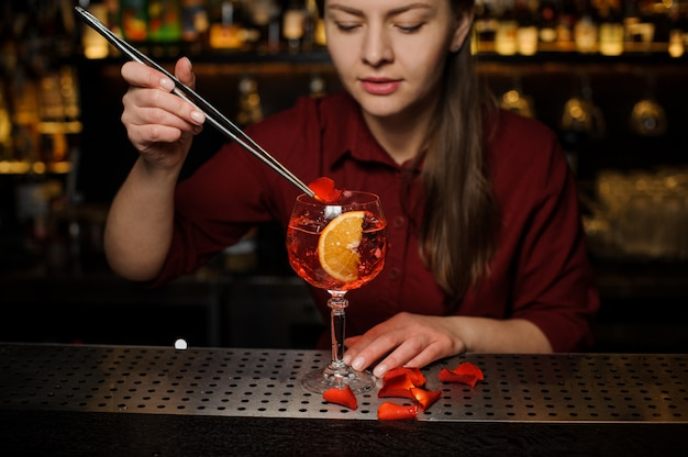Woman barman decorating a glass of aperol syringe cocktail with rose petals