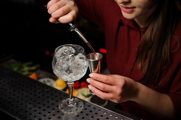 Woman barman pouring bitter for making an aperol syringe cocktail