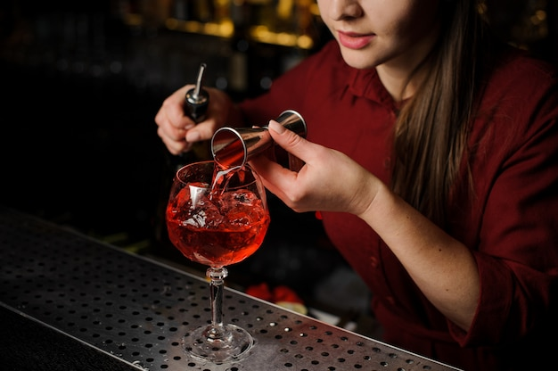 Woman bartender pouring bitter into a glass for making an aperol syringe cocktail