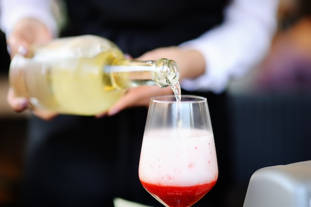 Woman bartender pours aperitif into glass