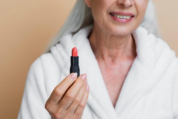 Woman in bath robe holding lipstick