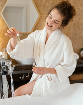 Woman in bath robe preparing bathtub